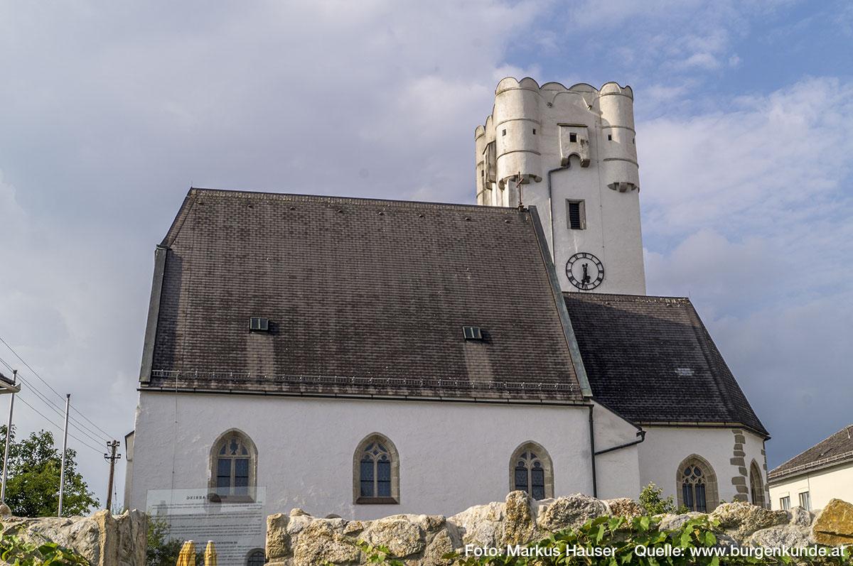 Die Kirche in Arbing mit dem Kirchturm aus der Zeit um 1510, dessen Aufsatz mit den Ecktürmchen, Erkern und Rundbogenzinnen datiert um 1600.
