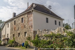 Ansicht der Kirche Arbing mit dem Mauerprojekt nach Entwürfen von Gottfried Kranzl. An die Dorfmauer schließt sich noch ein Gebäude mit unverputzter Südseite an, die auf das hohe Alter hinweist.