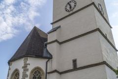 Der Aufsatz des Kirchturms mit Ecktürmchen, Erkern und Rundbogenzinnen datiert um 1600. Der Turm selbst und der Chor stammen aus der Zeit um 1510.
