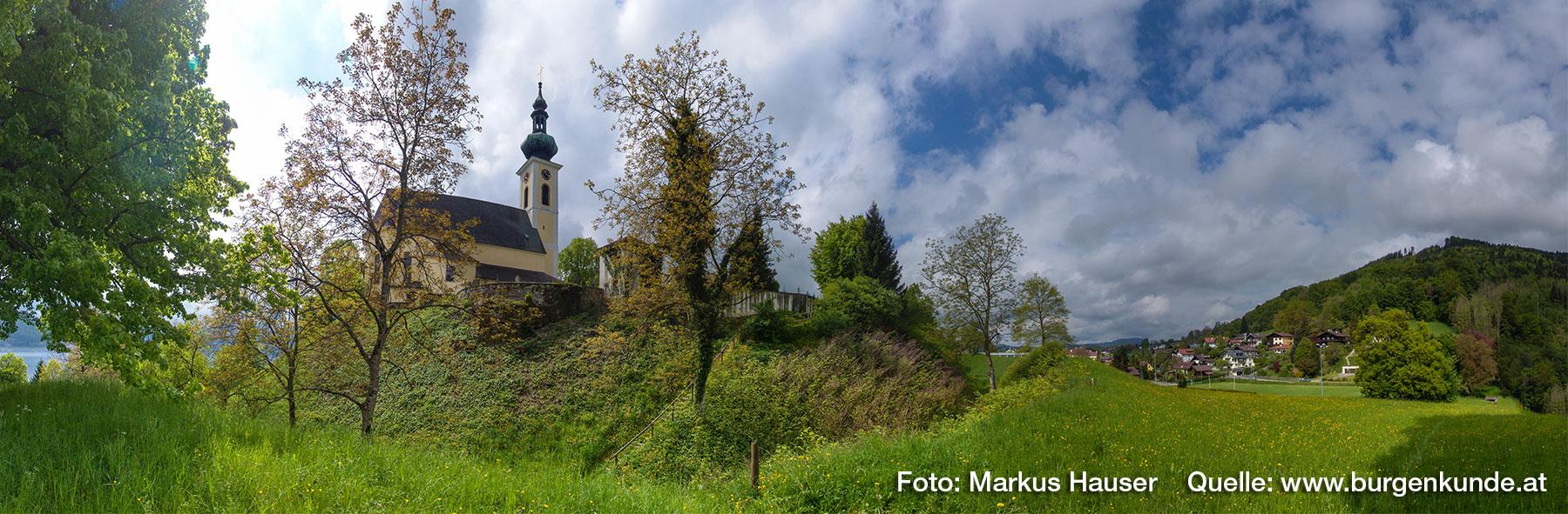 Der Kirchberg in Attersee, hier wird die karolingische Pfalz, der Königshof Atarhova, vermutet. Rechts der Buchberg, auf dessen Plateau sich eine Ringwallanlage befindet.