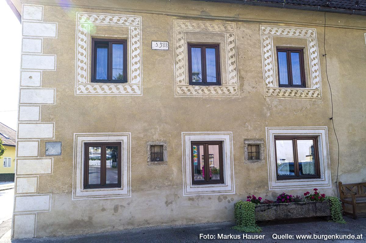 Zwischen den modernen Fenstern befinden sich zwei kleine fast quadratische (Fenster-)Öffnungen mit schmiedeeisernen Gitter. Im oberen Stock befindet sich schwarz gerahmt auf weißem Grund die Jahreszahl 1588.