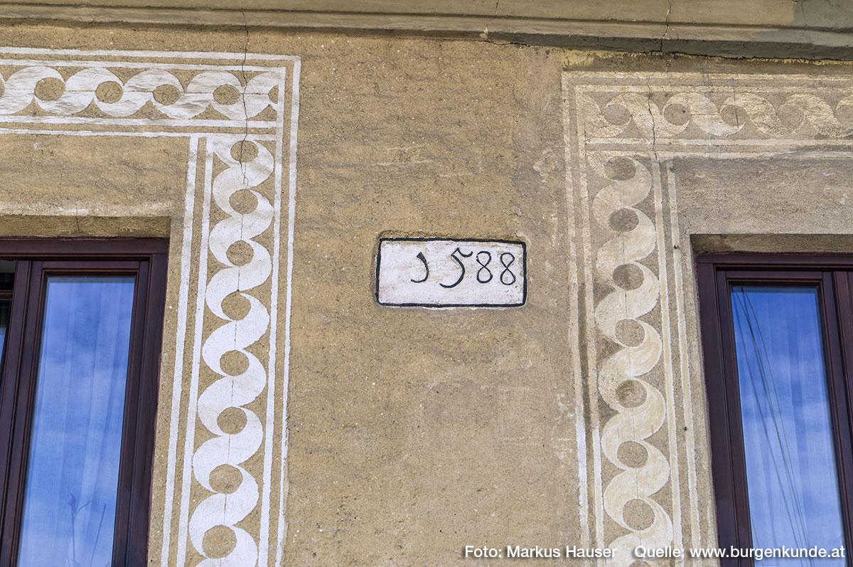 Im oberen Stock befindet sich schwarz gerahmt auf weißem Grund die Jahreszahl 1588.