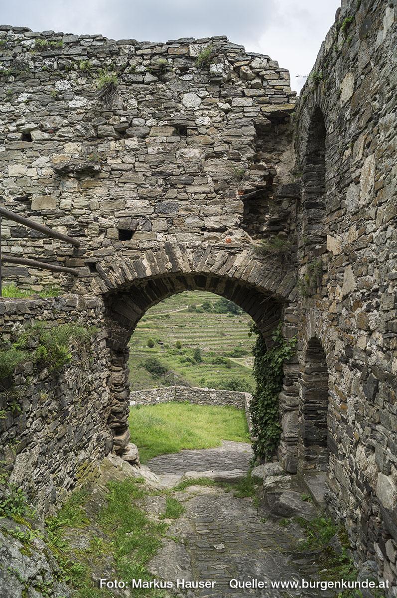 Ober dem Tor sind einige eckige Ausnehmungen im Mauerwerk erkennbar. Es könnte sich hier um die Löcher für die Stützbalken eines Wehrganges handeln.