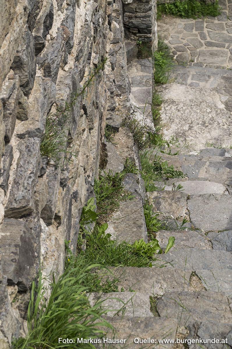 Das Fundament des Turmes springt im Bereich des Innenhofes gegenüber dem aufgehenden Mauerwerk schräg hervor.