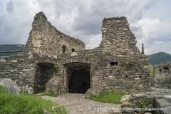 Dies sind die ruinösen Reste des einst stolzen und bemerkenswert hohen Palas. Der große Zugang rechts führte zu einem kellerartigen Raum, der allerdings auf der anderen Seite wieder verlassen werdn konnte. Der durch die Brücke überspannte Durchgang links führt zum Brunnen und einigen kleineren Räumen an der Nordwestseite der Hauptburg.