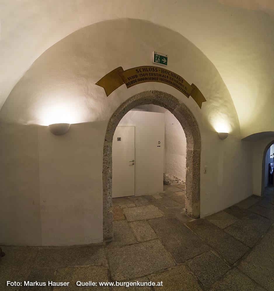 """Im ebenerdigen Mittelgang führt ein großes rundes Tor zum einstigen Verlies und dem darunter liegenden """"tiefen Keller"""". Früher war im Verlies das """"Heurigen Stüberl"""", heute sind die Toilettenanlagen untergebracht."""
