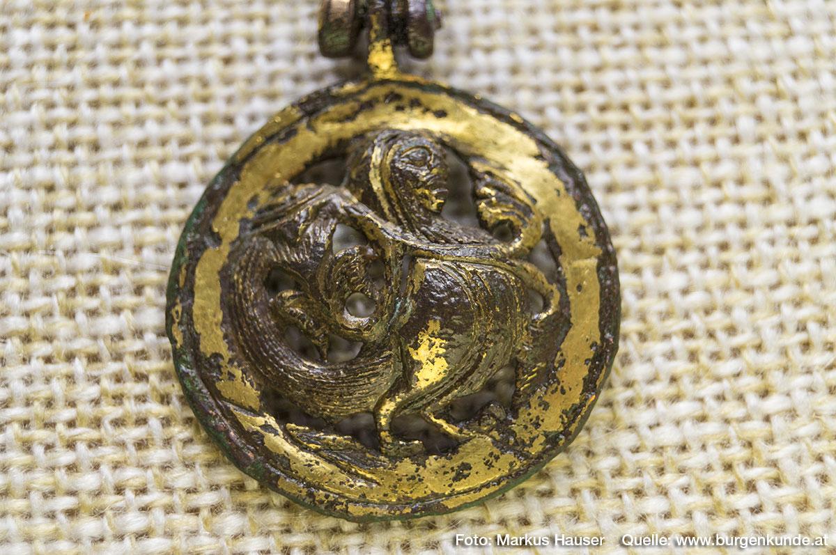 Einen absoluten Sensationfund machte die Archäologie vor Jahrzehnten am Burgstall Kögerl. Zwei vergoldete Schmuckscheiben. Hier im Bild: ein zweifüßiger, nach rechts schauender, Greif (Harpyie) mit Menschenkopf. Material Kupfer vergoldet.
