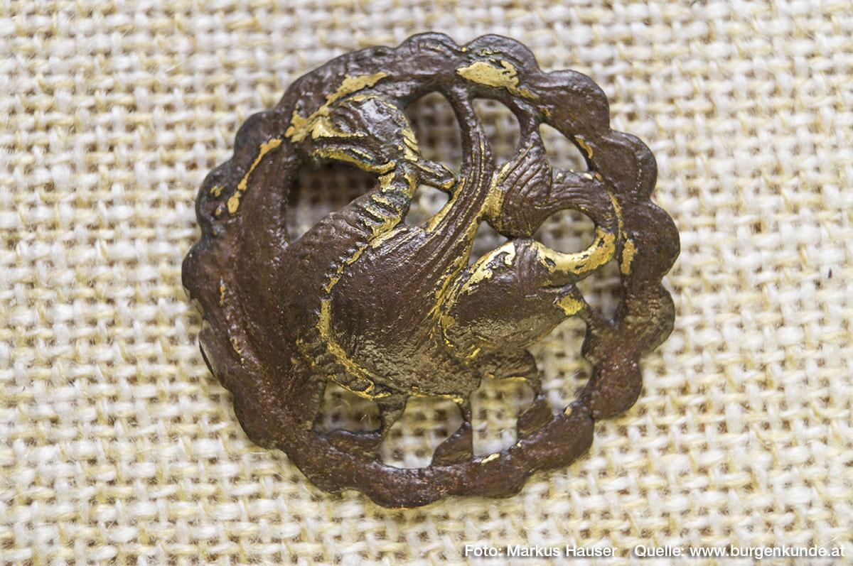 """Einen absoluten Sensationfund machte die Archäologie vor Jahrzehnten am Burgstall Kögerl. Zwei vergoldete Schmuckscheiben. Hier im Bild: ein vierfüßiger, nach links schreitender Vogel aus dessen Maul ein """"Lebensblatt"""" hängt. Material Kupfer vergoldet."""