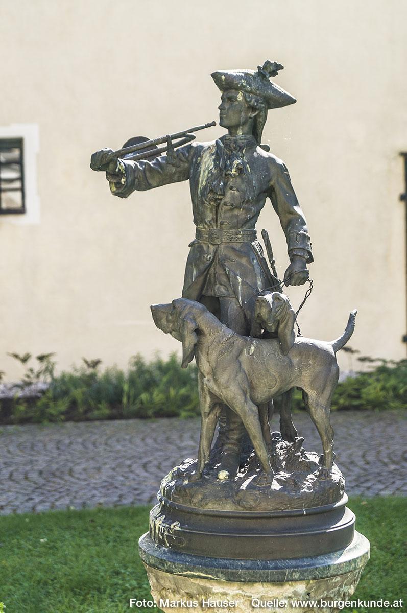 In der Mitte vorm Schloss befindet sich ein Brunnen samt jagdhornblasenden Jägerfigur mit Hunden.