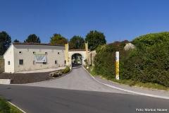 Zugang zum Schlosspark erlangt man über dieses Tor, das von einem älteren Steingebäude mit Schlüsselscharten flankiert wird. Daran schließt sich eine lange Mauer, die das gesamte Areal umfasst.