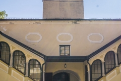 Links und rechts des Durchganges zum Arkadenhof die Aufgänge zum verglasten Obergeschoß.