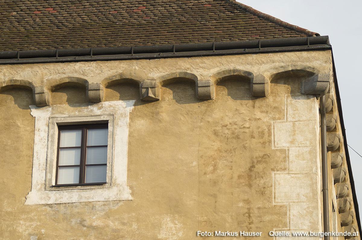 Direkt unter dem Walmdach der umlaufende Stichbogenfries auf Kragsteinen. Von diesen sticht einer besonders hervor.