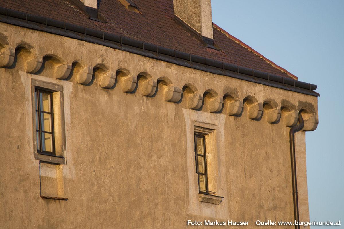 Direkt unter dem Walmdach ein umlaufender Stichbogenfries auf Kragsteinen. Beim linken Fenster ist unterhalb eine Vertiefung in der Mauer zu erkennen. Für welchen Zweck, bleibt unklar.