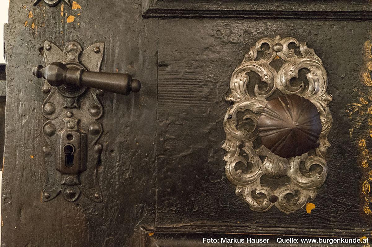 Besonders diese barocke Türe weist zahlreiche liebevolle Details und eine ganz besondere Bemalung auf. Auch Beschläge und Türgriffe sind bis ins Detail verziert.