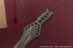 Das durchlöcherte Griffstück des Griffzungenschwertes aus Bronze.