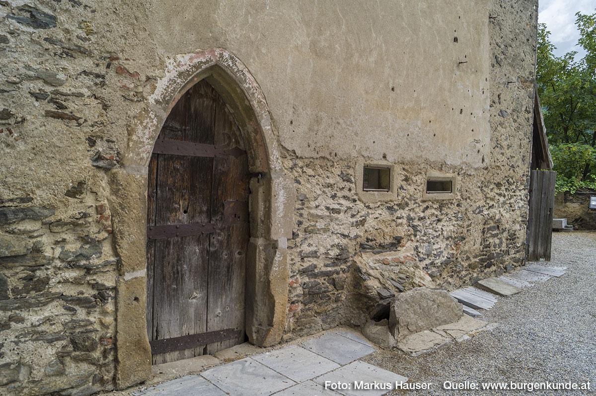 Neben der gotischen Eingangstüre in die Kapelle befinden sich noch zwei schmale, schlitzartige Öffnungen.