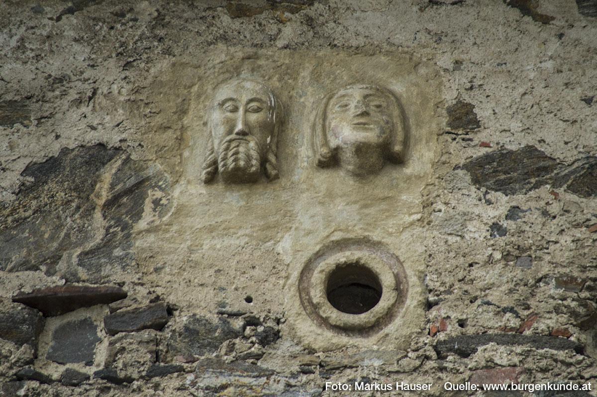 An der Südseite ist diese ganz besondere Seltenheit zu finden. Zwei romanische Reliefköpfe aus der Zeit um 1100 unterhalb der Dachrinne. Der Mann hat lange Haare und Vollbart, beides zu Zöpfen gedreht. Die Frau hat einen kinnlangen Pagenschnitt. Darunter eine kreisrunde Öffnung die ebenfalls aus dieser Zeit stammen dürfte.