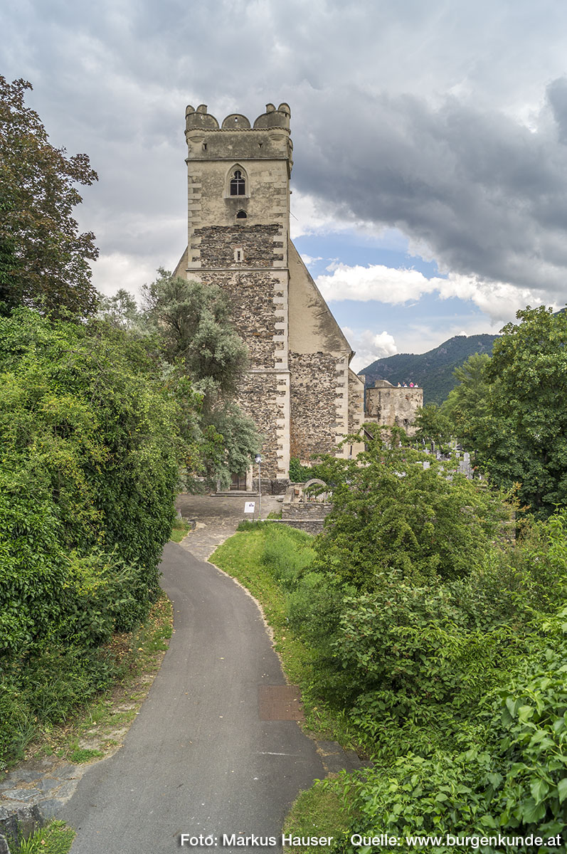 Die Wehrkirche St. Michael von Westen gesehen. Hier ist auch die jahrhundertelang genutzte alte Straße zu sehen, die sich zwischen der Wehrkirche und dem Michaeler Berg entlang schlängelt.