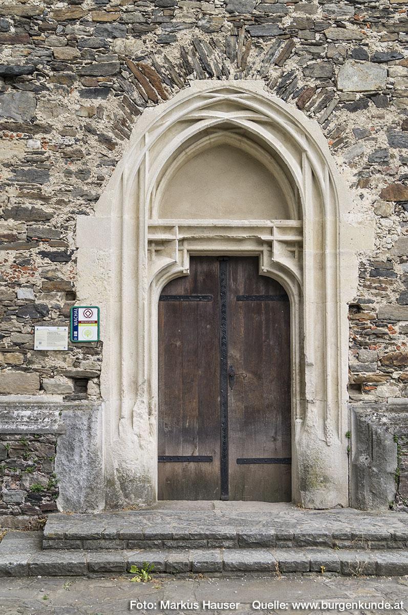 Der Turm an der Westseite besitzt ebenfalls einen Zugang durch dieses mehrfach gestäbte, gotische Eingangsportal mit Schulterbogenschluß.