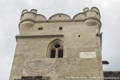 Der Turm der Wehrkirche mit kleinen runden Ecktürmchen, Rundzinnen und einem gotischen Fenster im oberen Bereich. Darunter eine Sonnenuhr und neben den Fenster sind die Füße eines Adlers zu sehen (vll. der Doppeladler?).